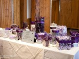 an ivory and purple candy table with various types of candies in bold purple