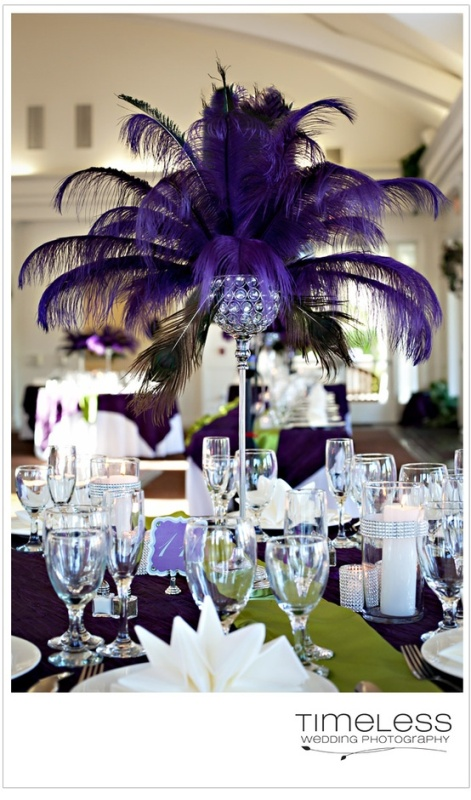 a purple tablecloth and a centerpiece made of of bright purple feathers