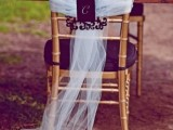 purple florals and a purple chair with tulle and signage to add color to the reception