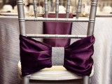 a silver chair with a deep purple bow and embellishments plus a purple napkin for an exquisite touch