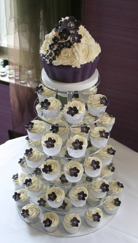 a wedding cake designed as a giant cupcake in neutrals and purple and real cupcakes with purple sugar blooms on top