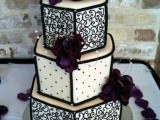 a black and white patterned wedding cake topped with purple flowers