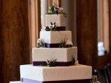 a white patterned wedding cake decorated with purple ribbons