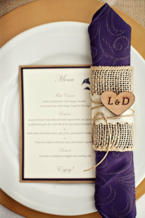 a purple patterned napkin with a burlap napkin ring and a monogrammed heart