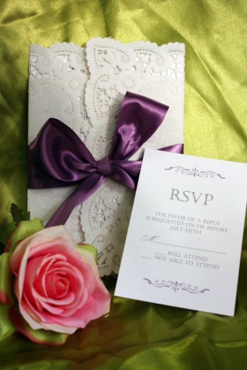 white lace wedding stationery with a silk purple bow
