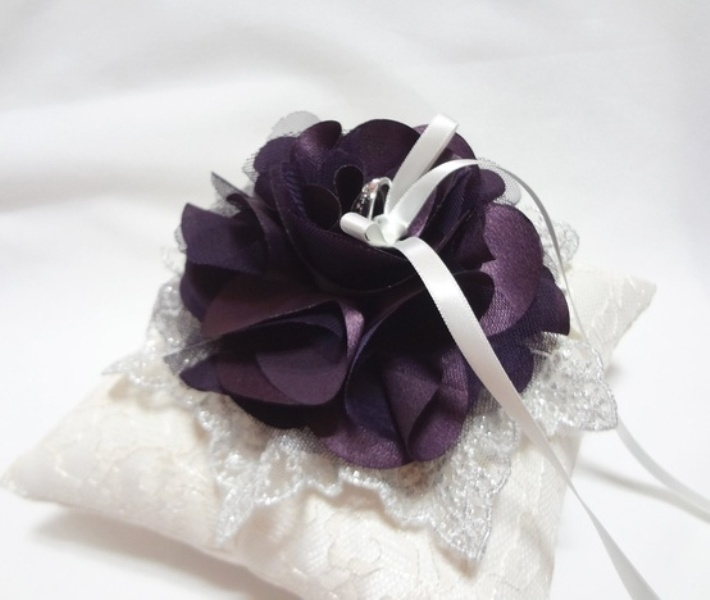 a white lace ring pillow decorated with purple fabric flowers is a stylish way to deliver the rings