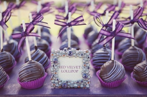 delicious chocolate cake pops with purple liners and purple bows on top