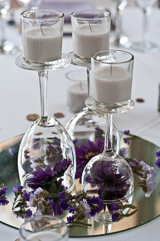 a wedding centerpiece of glasses with candles and with purple blooms inside