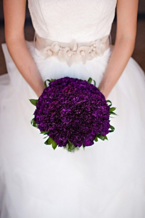 a deep purple wedding bouquet with touches of green