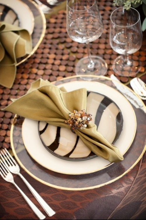 a creative wedding tablescape with a wooden runner, sheer, white and zebra plates, a bold napkin with an embellished napkin ring and a leafy placemat