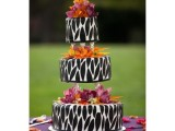 a catchy wedding cake of three parts with safari prints and bold blooms is a lovely idea with much boldness
