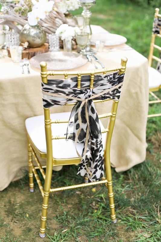 safari themed wedding reception with gold chairs with leopard covers is a cool and bold idea