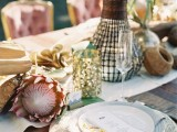 a safari wedding tablescape with king proteas, candles, gold candleholders, woven charger and simple cutlery