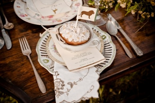 a safari inspired wedding tablescape with vintage chargers and plates, with printed linens, greenery and blooms and a cake in a cup topped with a lion