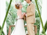 a safari tropical wedding arch of bamboo and with greenery and blooms is a bold and fun idea