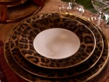 a safari wedding tablescape with leopard plates with a gold edge, candles, woven chargers and glasses