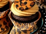 chocolate cupcakes with frosting and a leopard cookie on top is a fun and bold idea of a wedding dessert
