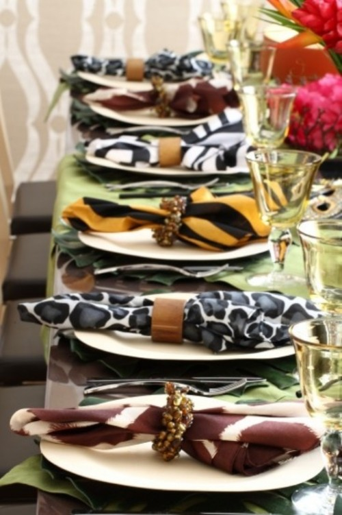 a bright safari-themed wedding table with tropical leaves, white plates and safari-themed napkins with embellished napkin rings and yellow glasses