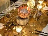 a safari-themed wedding table with a burlap runner, candles and a king protea in a concrete planter, greenery and twigs, simple cutlery
