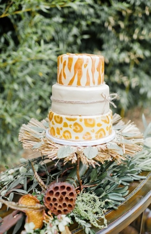an eye-catchy safari wedding cake with a plain white, zebra and leopard print tiers, served with greenery and husks