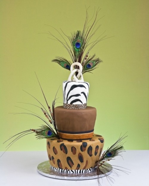 a bright safari wedding cake with a zebra, leopard and brown tier, with peacock feathers and twigs looks unique