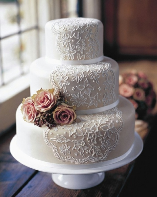 a tan wedding cake with white lace decor and pink fresh blooms is a gorgeous idea with a classic feel