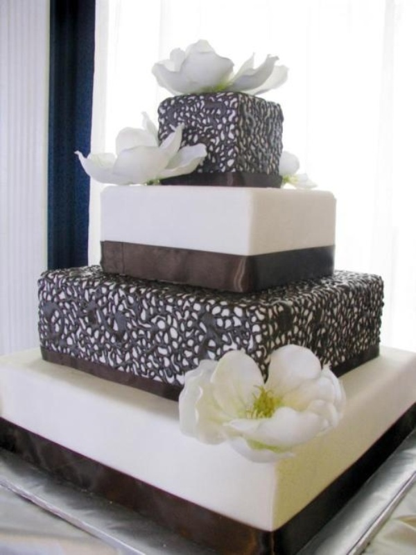 a white and usual chocolate wedding cake decorated with ribbons and two tiers covered with chocolate lace plus sugar blooms