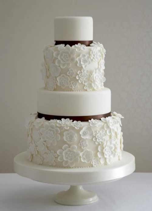 a white wedding cake with two floral tiers and two sleek ones plus brown ribbons looks ethereal