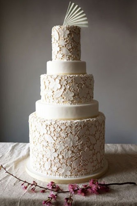 a large neutral floral lace wedding cake with some sleek tiers and a sugar fan on top is a very whimsy idea