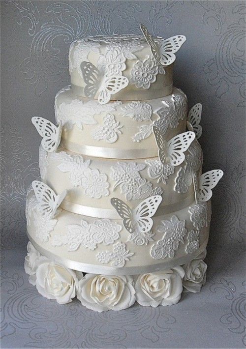 a neutral floral lace wedding cake decorated with sugar butterflies is a very chic and girlish idea