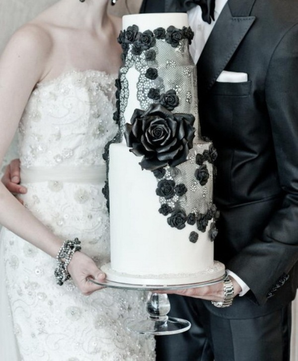a white wedding cake with black lace and florals is a chic idea for a black and white wedding