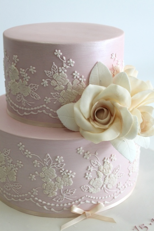a blush wedding cake with white lace, sugar blooms and a ribbon bow on the bottom is a very cute idea