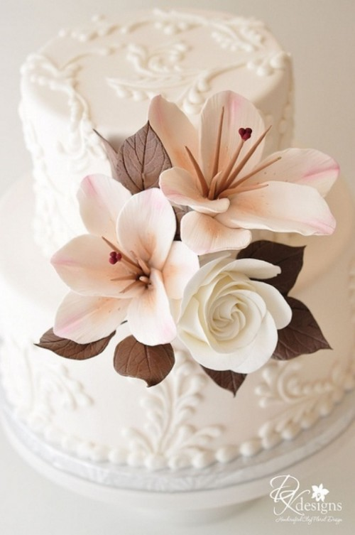 a white lace wedding cake with sugar blooms and leaves looks fresh and cool for a spring or summer wedding