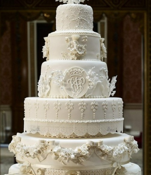 an ivory cakery masterpiece with lace, ruffle and floral decor plus beads all made of sugar