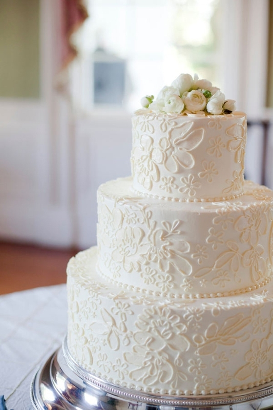 a white lace wedding cake topped with fresh white blooms is a beautiful and stylish idea