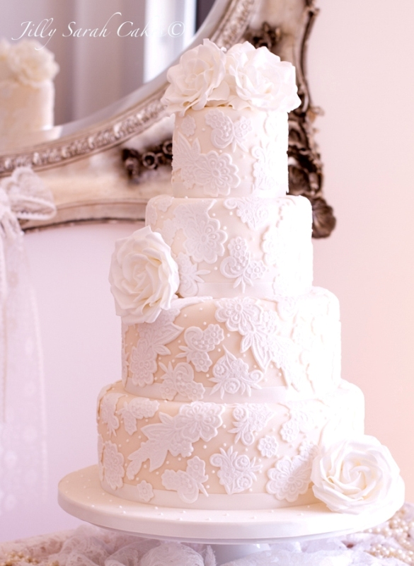 a white lace wedding cake with fresh white roses is timeless elegance with a chic feel