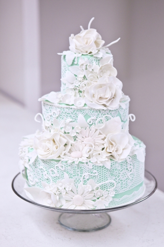 a mint wedding cake with white lace and white guar flowers is a very tender and chic idea for a spring wedding