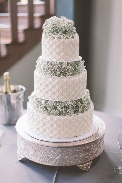 a white lace wedding cake with baby's breath in between is ideal for a rustic or vintage-inspired wedding