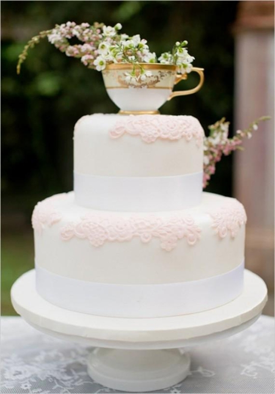 a white wedding cake with white ribbons, pink lace and some fresh blooms in a cup on top