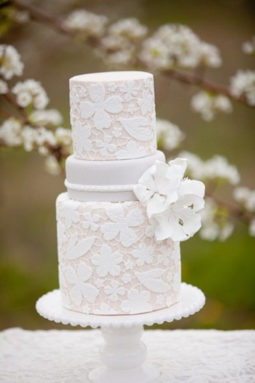 a neutral lace wedding cake with sugar blooms is a very beautiful and elegant option