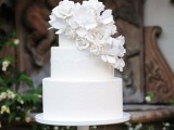 a white lace wedding cake decorated with cascading white sugar blooms is gorgeous and very unusual