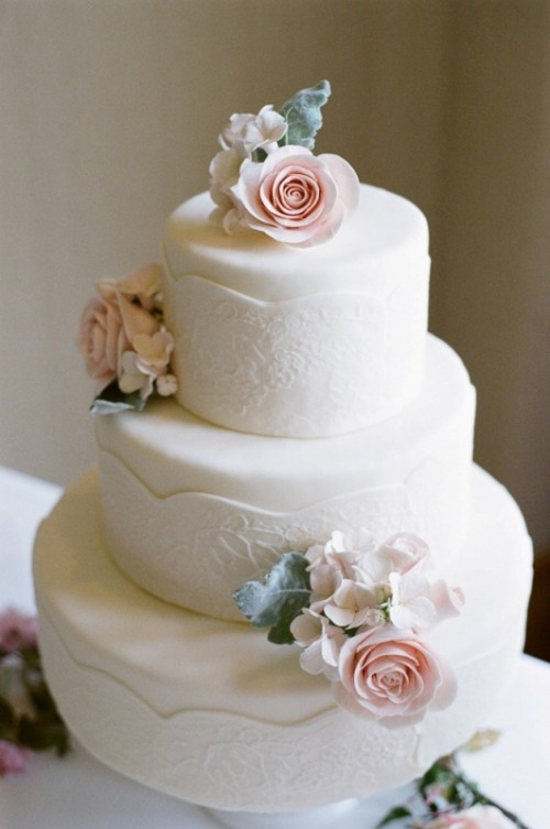 a white lace wedding cake decorated with sugar blooms in blush and white and greenery