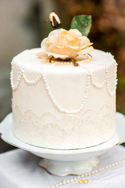 a white wedding cake decorated with sugar lace and pearls plus sugar blooms and leaves on top