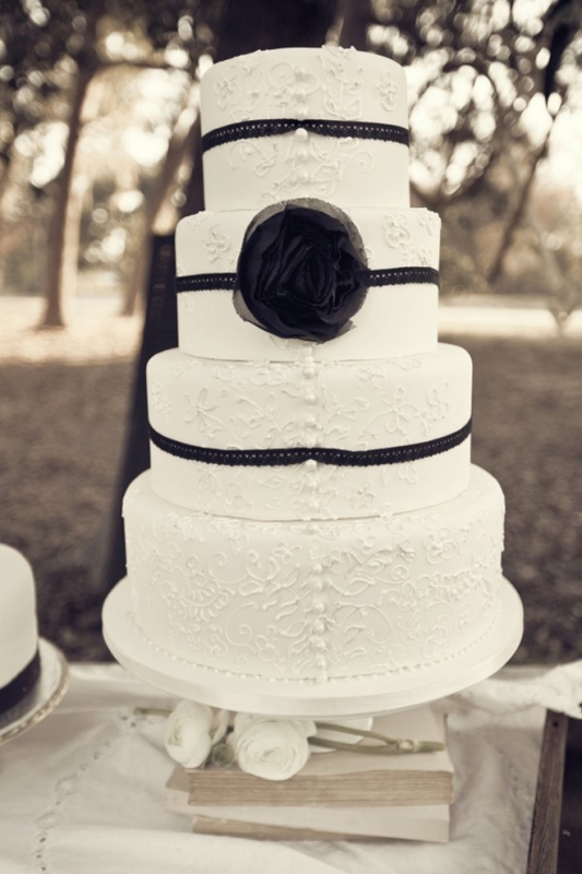a white lace wedding cake decorated with ribbons and a black fabric flower for a monochromatic vintage wedding