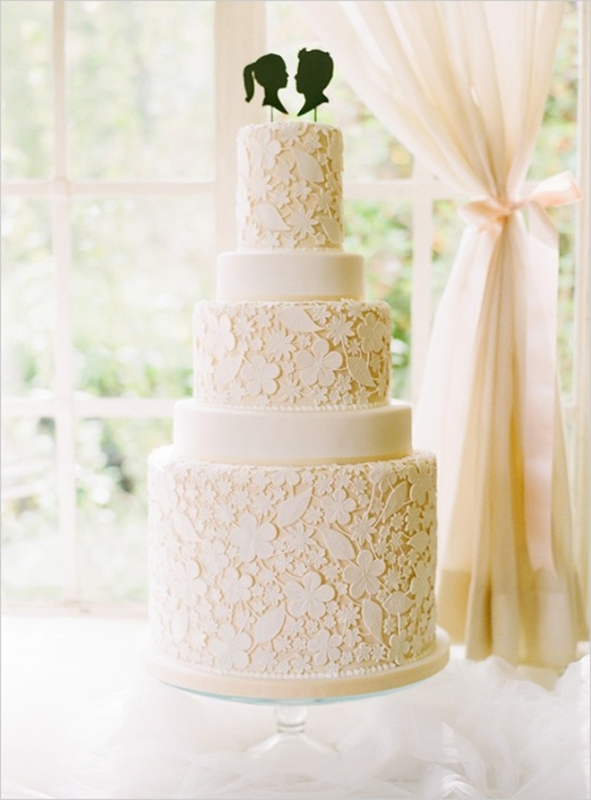 a tan wedding cake decorated with white edible lace and black head silhouettes as toppers for a catchy touch