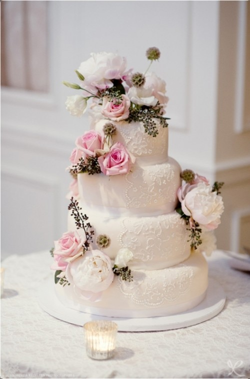 a white lace wedding cake topped with fresh pink and white blooms and greenery looks very catchy and very fresh