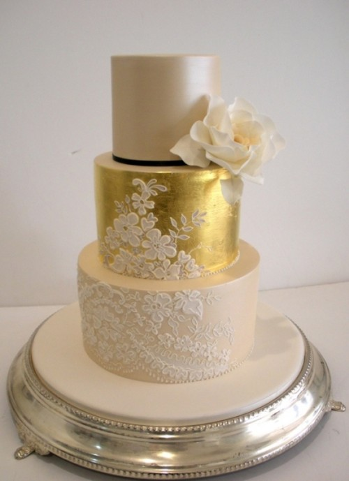 a tan and gold wedding cake decorated with white lace and a sugar bloom looks very glam-like