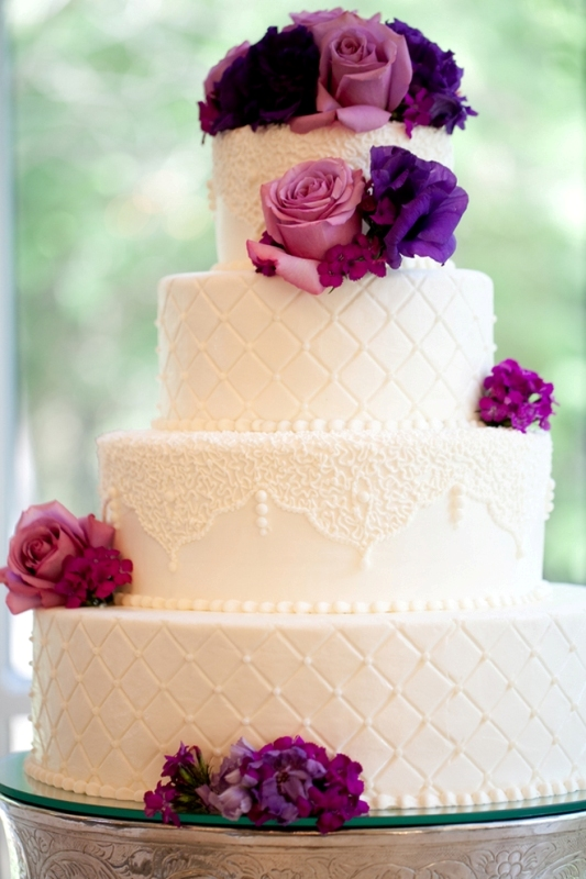 a white lace and tufted wedding cake decorated with purple and fuchsia fresh flowers