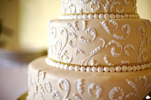 a tan wedding cake decorated with white lace and edible beads is a gorgeous idea
