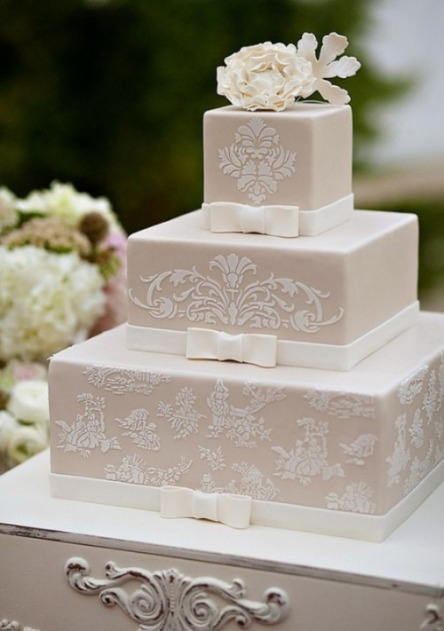 a square tan wedding cake decorated with white lace, ribbons and bows plus a sugar bloom on top
